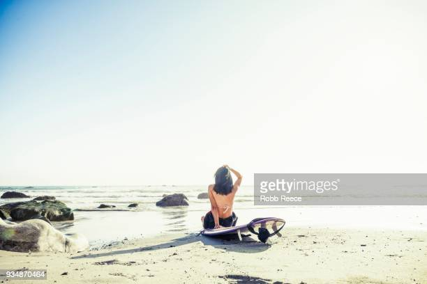 a woman surfer with a surfboard on a remote ocean beach - robb reece stockfoto's en -beelden