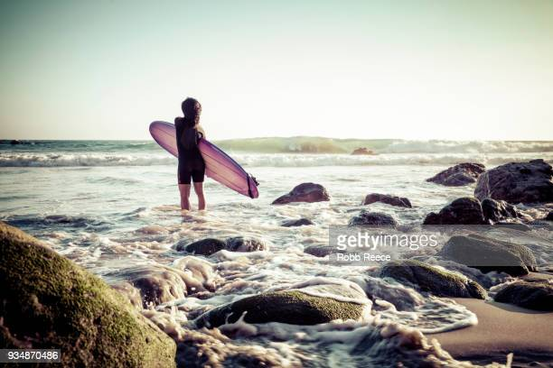 a woman surfer with a surfboard on a remote ocean beach - robb reece fotografías e imágenes de stock