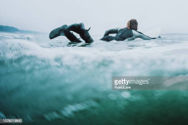 woman surfing at oregon coast on overcast day - paddling stock pictures, royalty-free photos & images