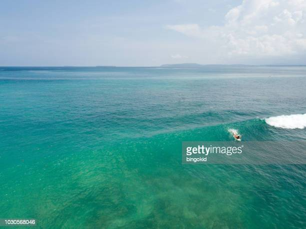 woman surfing from above - paddling stock pictures, royalty-free photos & images