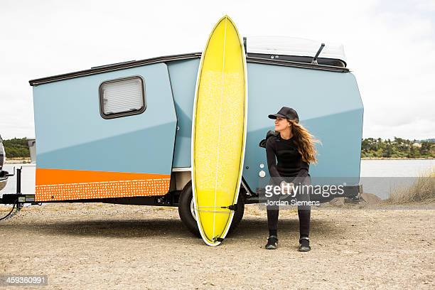 Woman surfing in a wetsuit.