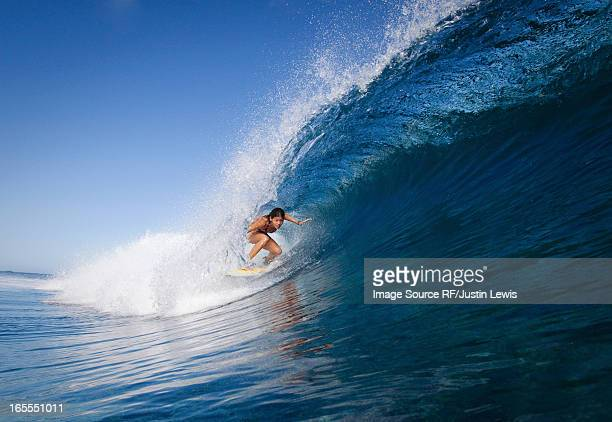Woman surfing in crest of wave