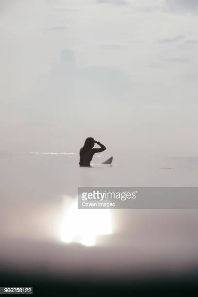 woman surfing in sea against sky during sunny day - seascape stock pictures, royalty-free photos & images