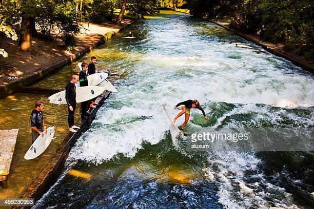 Mujer surf en el río Eisbach Munich, Alemania