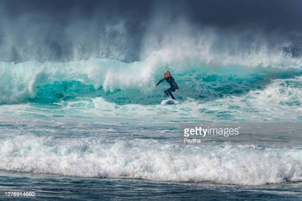 woman surfing on waves in tenerife, playa de las americas, spain - atlantic islands stock pictures, royalty-free photos & images