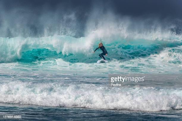 donna che naviga sulle onde a tenerife, playa de las americas, spagna - image foto e immagini stock
