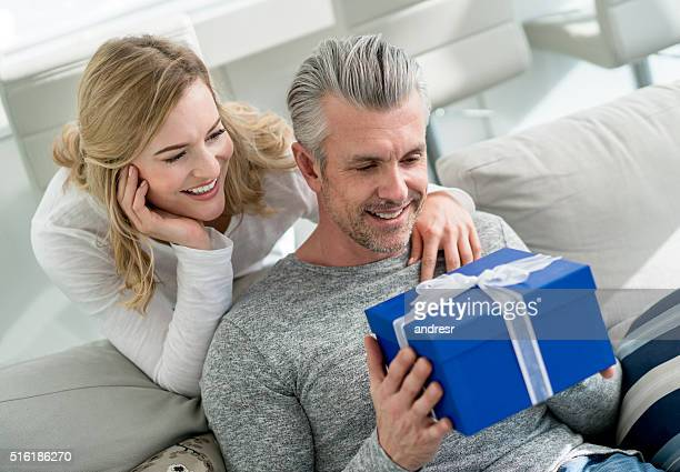 Woman surprising man with a present