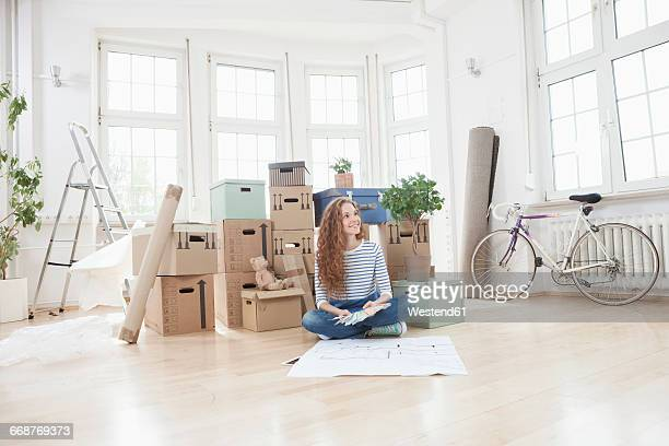 Woman surrounded by cardboard boxes sitting on floor with construction plan