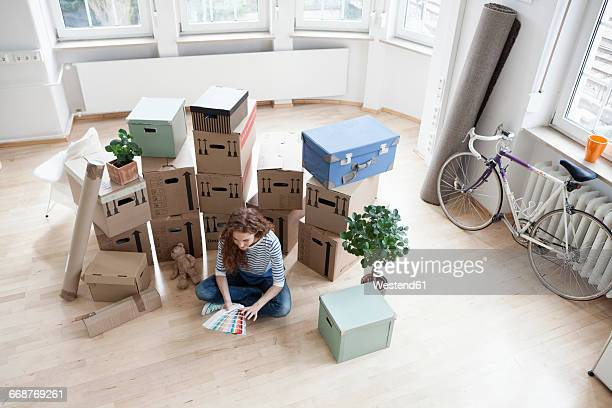 woman surrounded by cardboard boxes with color samples on floor - surrounding stock pictures, royalty-free photos & images