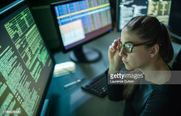 woman surrounded by monitors - crimine foto e immagini stock
