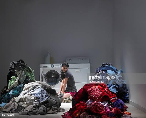 Donna circondata da montagne di lavanderia