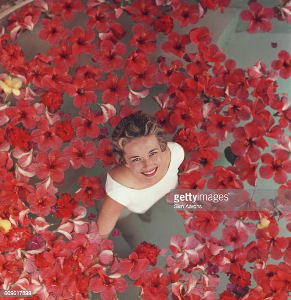 A woman surrounded by red hibiscus flowers in a swimming pool in Acapulco Mexico circa 1960