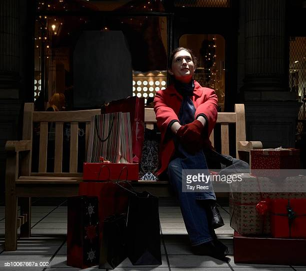 Woman surrounded with presents sitting on bench in shopping mall at night