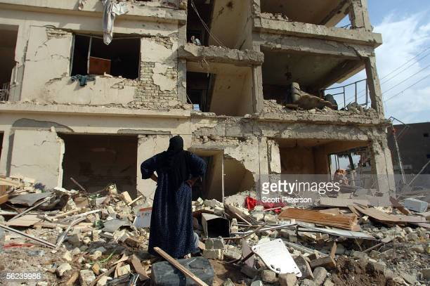Woman surveys the damage to her apartment, as Iraqis begin to clear up, one day after a double suicide car bomb attack struck near the Hamra Hotel, a...