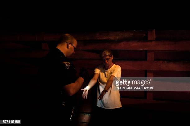 A woman suspected of acting under the influence of heroine shows her arms to Huntington Police Officer Dakota Dishman on April 19 2017 in Huntington...