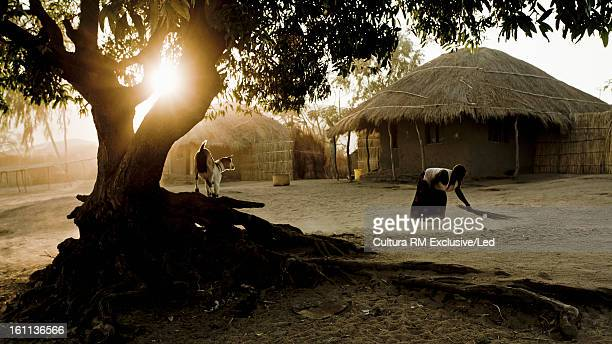 Woman sweeping around huts in village