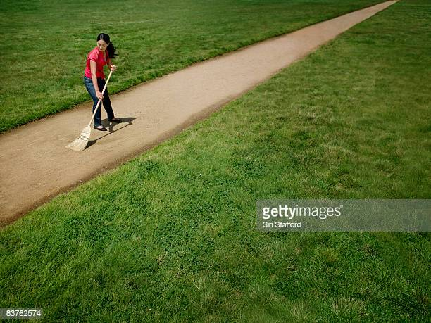 woman sweeping dirt path surrounded by grass - broom sweeping stock pictures, royalty-free photos & images