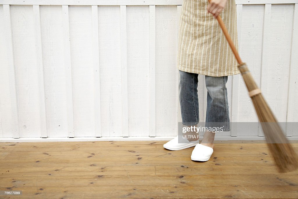 Woman sweeping floor using Japanese style broom in home : Stock Photo