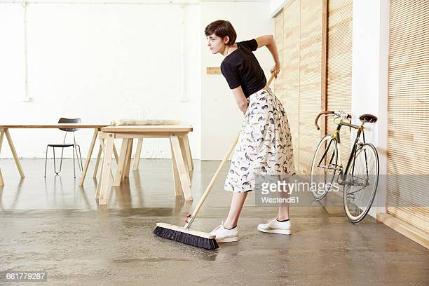 Woman sweeping in a studio