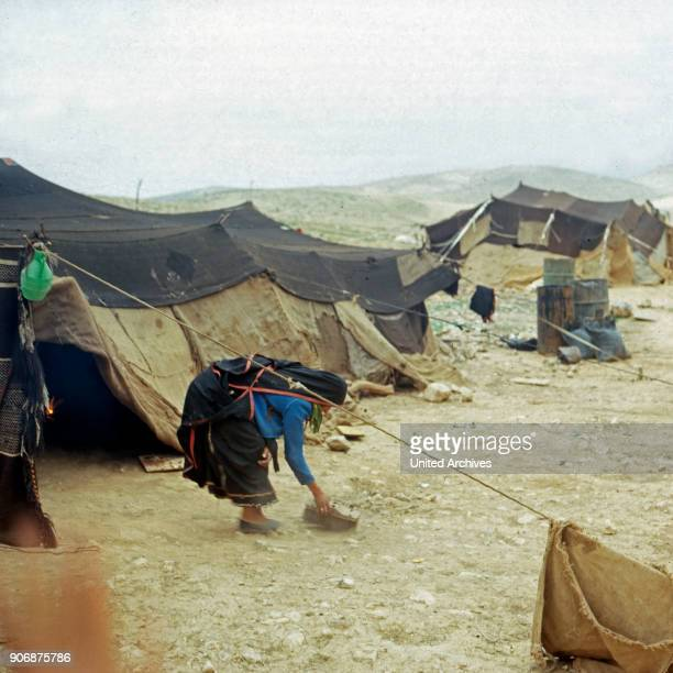 A woman sweeping in front of her tent at a bedouin camp Israel late 1970s