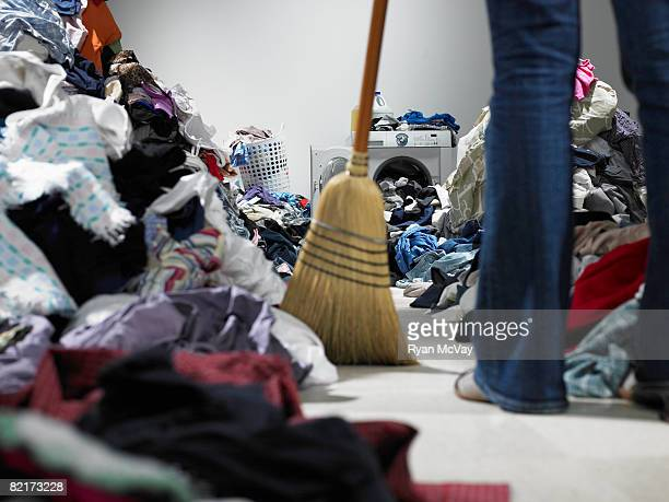 Woman sweeping pathway through piles of laundry