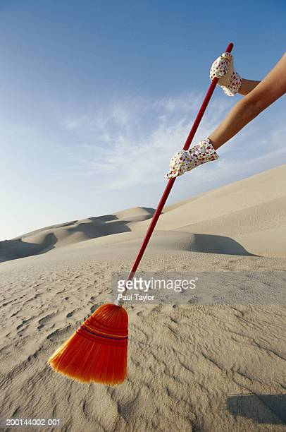 Woman sweeping sand dunes