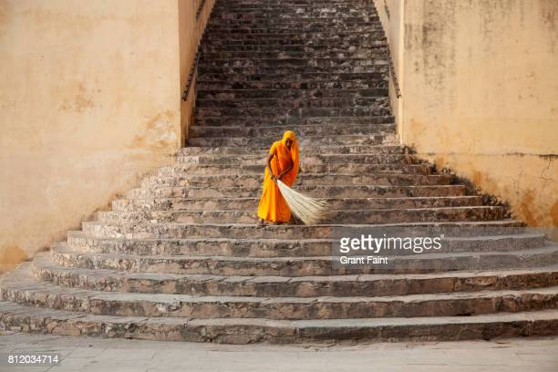 woman sweeping steps of fort. - sweeping stock pictures, royalty-free photos & images