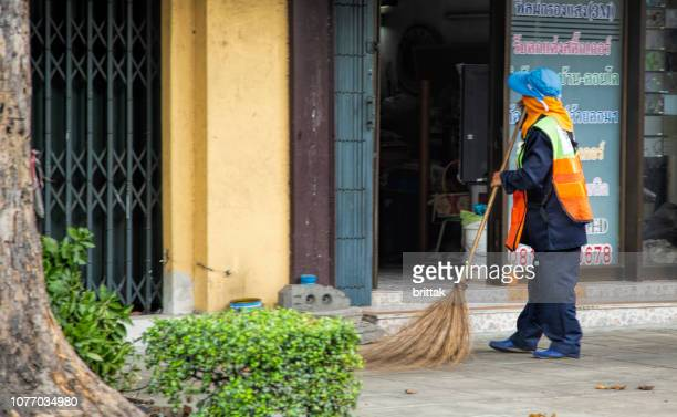 woman sweeping street in bangkok, thailand. - street sweeper stock pictures, royalty-free photos & images