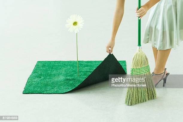 woman sweeping under artificial turf rug, waist down - sweeping stock pictures, royalty-free photos & images
