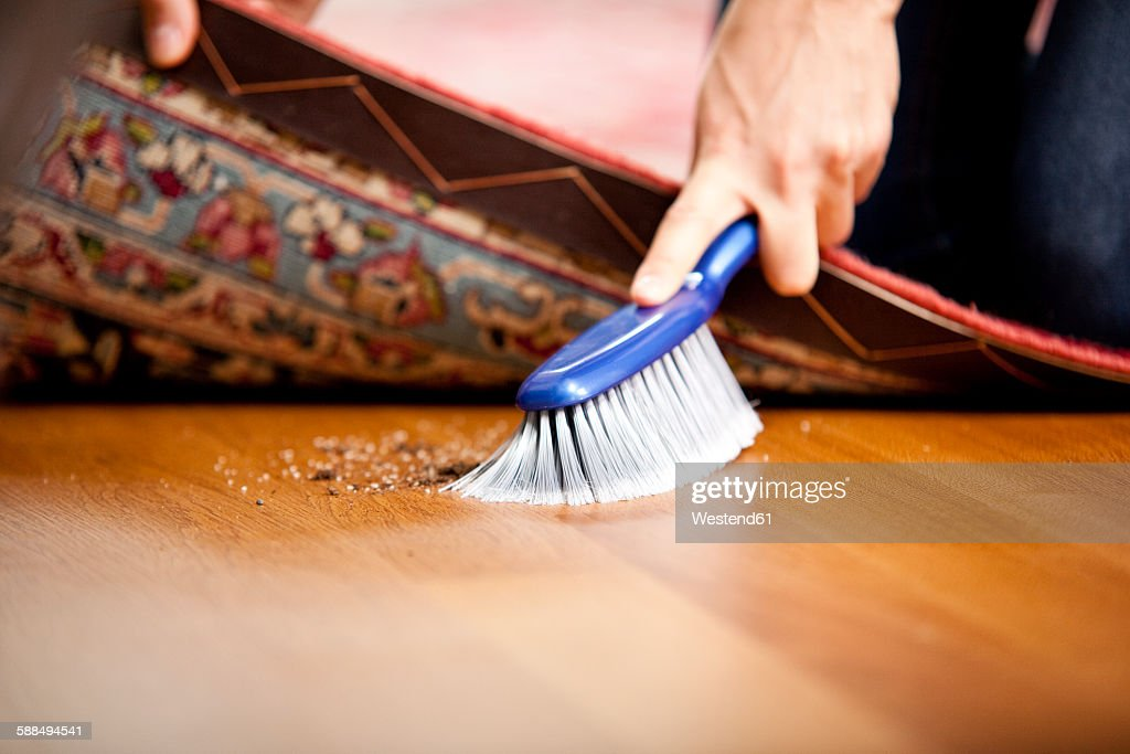 Woman sweeping under the carpet : Stock Photo