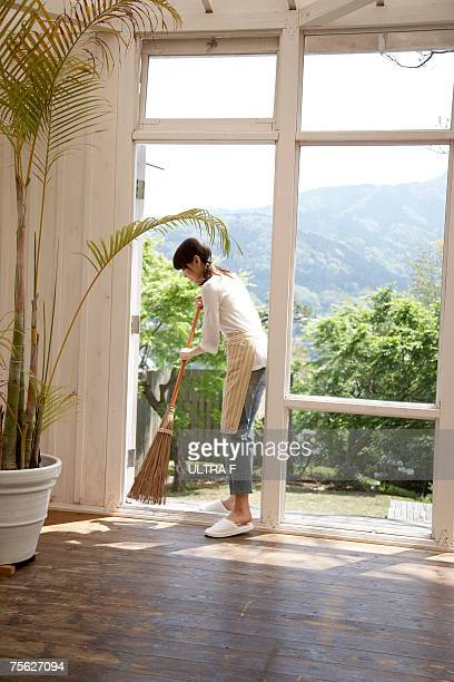 woman sweeping wooden floor using japanese style broom, in home - sweeping stock pictures, royalty-free photos & images