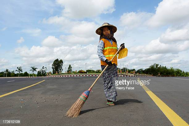 A woman sweeps a deserted Naypyidaw avenue