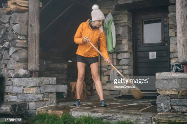 woman sweeps entry to stone hut in the mountains - broom sweeping stock pictures, royalty-free photos & images