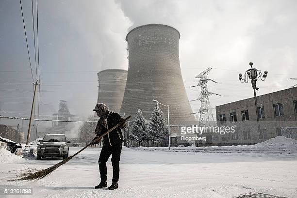 A woman sweeps in front of the cooling towers at a Tonghua Iron Steel Group Co plant in the Erdaojiang district in Tonghua Jilin province China on...