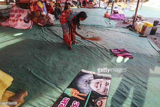 A woman sweeps the ground as a poster of Indian Prime Minister Narendra Modi sits inside a temporary suburban camp set up by local political party...