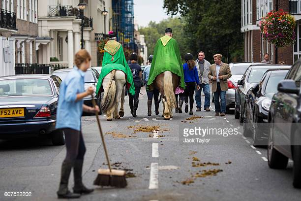 A woman sweeps up horse manure as members of the clergy leave on horseback following a church service outside St John's Church Hyde Park during the...