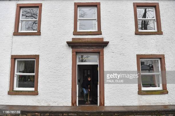 Woman sweeps water out of a residential building in Appleby, northwest England, on February 10, 2020 after flooding brought by Storm Ciara. - Storm...