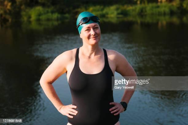 woman swimmer standing by a river - une seule femme d'âge mûr photos et images de collection