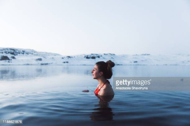 woman swimming at the thermal pool with view of beautiful snowcapped mountains in iceland - hot spring stock pictures, royalty-free photos & images