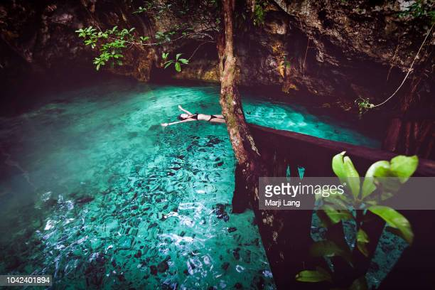Woman swimming in a cenote around Tulum Quintana Roo Mexico