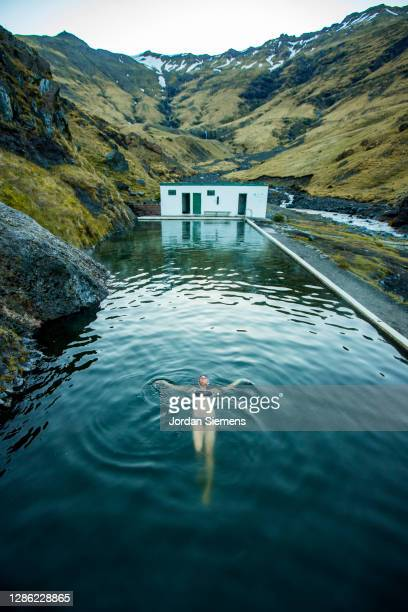 a woman swimming in a hot spring in iceland. - iceland stock pictures, royalty-free photos & images