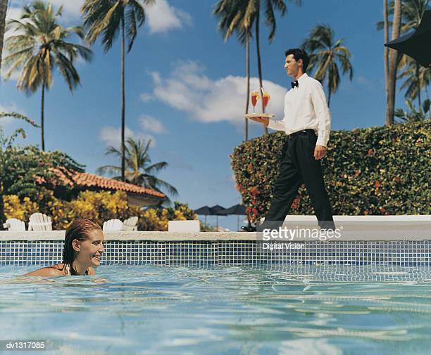 Woman Swimming in a Pool With a Waiter Carrying a Tray of Cocktails in the Background