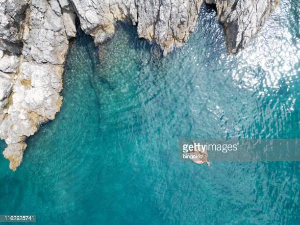 mujer nadando en aguas cristalinas hermosas - croacia fotografías e imágenes de stock