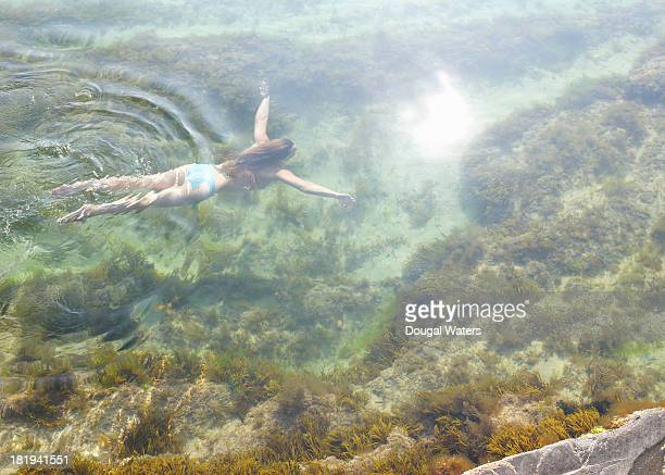 Woman swimming in idyllic rock pool.