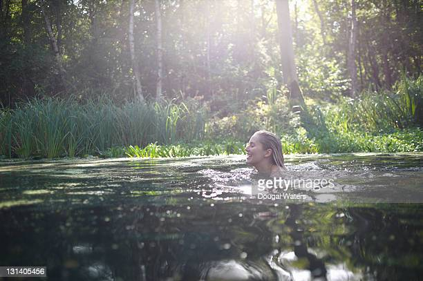Woman swimming in natural lake.