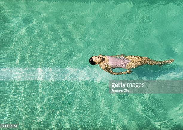 Woman swimming in pool, full length