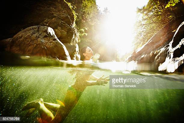 Woman swimming in river on summer afternoon
