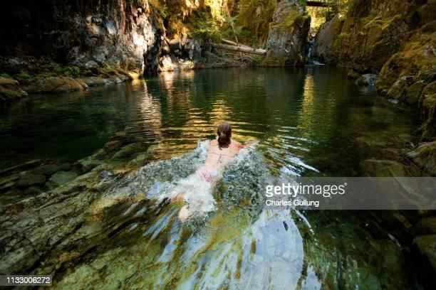 woman swimming in river - lagune stockfoto's en -beelden