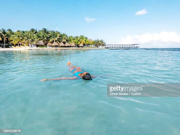 woman swimming in sea against sky - playa del carmen stock pictures, royalty-free photos & images