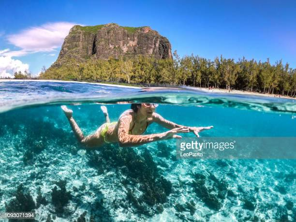 mujer nadando en la mar bella de mauricio protegido por el arrecife en el océano índico - islas mauricio fotografías e imágenes de stock